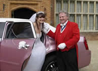 Toastmaster assisting bride from wedding car
