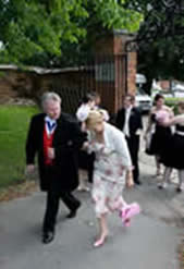 Toastmaster Richard Palmer assisting a brides mother into the church, picture is courtesy of Essex wedding photographer Dave Court