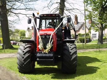 Bridegroom arriving by tractor to Essex Wedding