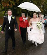 Toastmaster Richard Palmer assisting the bride into the wedding reception ensuring the wedding dress does not spoil in the rain!